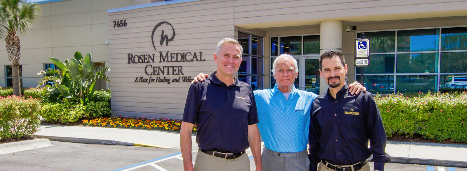 Harris Rosen,Ashley Bacot, and Kenneth A. Aldridge in front of the Medical Center building