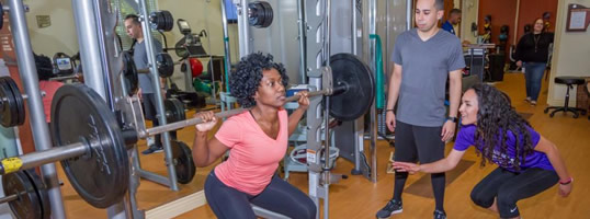 Women doing squats on smith machine with help of a trainer